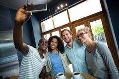 Groupe d'amis prenant un selfie de téléphone portable Images libres de droits