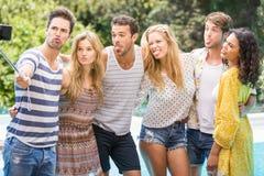 Groupe d'amis prenant un selfie près de la piscine Images libres de droits