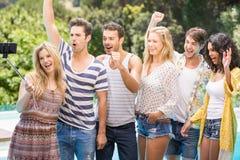Groupe d'amis prenant un selfie près de la piscine Images stock