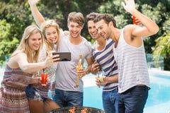 Groupe d'amis prenant un selfie près de la piscine Photos libres de droits