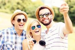 Groupe d'amis prenant une photo en parc Photographie stock libre de droits