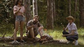 Groupe d'amis rôtissant des guimauves sur le feu de camp Amis rôtissant la guimauve douce sur un feu le soir dans clips vidéos