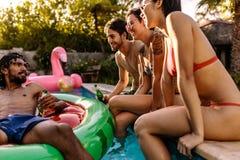 Groupe d'amis refroidissant à la réception au bord de la piscine Photo stock
