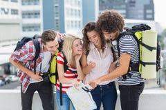 Groupe d'amis regardant dans le téléphone portable Photo stock