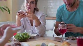 Groupe d'amis regardant des smartphones pendant le dîner à la maison banque de vidéos