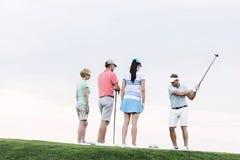Groupe d'amis regardant l'homme jouant le golf contre le ciel clair Photos stock