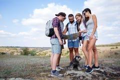 Groupe d'amis regardant la carte et la discutant dehors Les amis s'attaquent à la hausse, forêt, récréation, aiment le mode de vi Photos stock