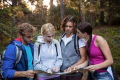 Groupe d'amis regardant la carte tout en augmentant Image libre de droits