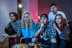 Groupe d'amis regardant la TV assortir à la maison Photo libre de droits