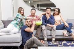 Groupe d'amis regardant la TV et mangeant du maïs éclaté sur le sofa Photo stock