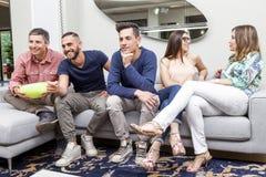 Groupe d'amis regardant la TV et mangeant du maïs éclaté sur le sofa Image libre de droits