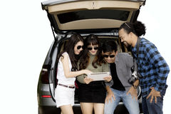 Groupe d'amis regardant le comprimé numérique Photo stock