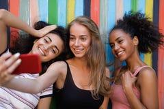 Groupe d'amis regardant le téléphone intelligent Image libre de droits