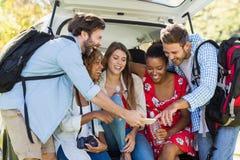 Groupe d'amis regardant le téléphone portable Photo libre de droits