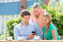 Groupe d'amis regardant le téléphone portable Photos libres de droits