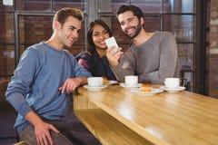 Groupe d'amis regardant leur smartphone Photographie stock libre de droits