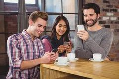 Groupe d'amis regardant leur smartphone Image libre de droits