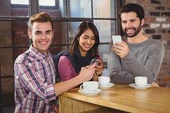 Groupe d'amis regardant leur smartphone Photo libre de droits