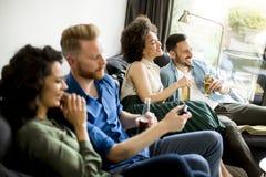 Groupe d'amis regardant TV, cidre potable et ayant l'amusement Image libre de droits