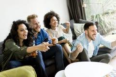 Groupe d'amis regardant TV, cidre potable et ayant l'amusement Photos stock