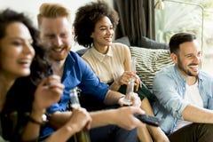 Groupe d'amis regardant TV, cidre potable et ayant l'amusement Images stock