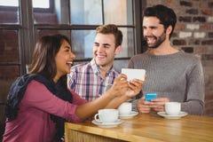Groupe d'amis regardant un smartphone Images libres de droits