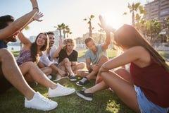 Groupe d'amis reposant l'extérieur donnant la haute cinq Photo stock