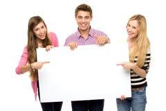 Groupe d'amis retenant la plaquette blanc Photographie stock