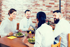Groupe d'amis riants mangeant au restaurant et à la causerie Image stock