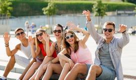 Groupe d'amis riants s'asseyant sur la place de ville Photos stock