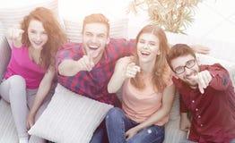 Groupe d'amis riants s'asseyant sur le sofa et montrant l'index Photos stock
