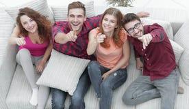 Groupe d'amis riants s'asseyant sur le sofa et montrant l'index sur l'appareil-photo Images libres de droits