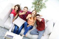Groupe d'amis riants s'asseyant sur le sofa et montrant l'index sur l'appareil-photo Image stock