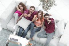 Groupe d'amis riants s'asseyant sur le sofa et montrant l'index sur l'appareil-photo Photos libres de droits
