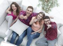 Groupe d'amis riants s'asseyant sur le sofa et montrant l'index sur l'appareil-photo Photographie stock libre de droits