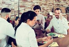 Groupe d'amis sérieux occupés avec le téléphone dans le restaurant Photo libre de droits