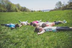 Groupe d'amis s'étendant dans l'herbe Image libre de droits