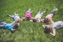 Groupe d'amis s'étendant dans l'herbe Photos stock