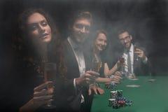 Groupe d'amis s'asseyant à la table de jeu dans le casino Images stock