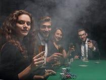 Groupe d'amis s'asseyant à la table de jeu dans le casino Photographie stock libre de droits