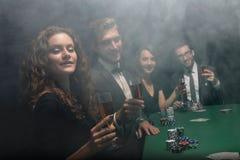 Groupe d'amis s'asseyant à la table de jeu dans le casino Photographie stock