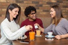 Groupe d'amis s'asseyant au café tandis que deux flirtent Photographie stock libre de droits