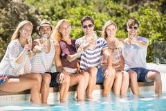 Groupe d'amis s'asseyant au poolside avec le verre de champagne Photos libres de droits