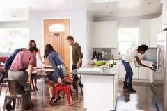 Groupe d'amis s'asseyant au Tableau pour le dîner à la maison Photographie stock libre de droits