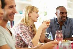 Groupe d'amis s'asseyant autour du Tableau ayant le dîner Photo stock
