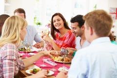 Groupe d'amis s'asseyant autour du Tableau ayant le dîner Image libre de droits