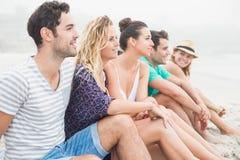 Groupe d'amis s'asseyant côte à côte sur la plage Image stock
