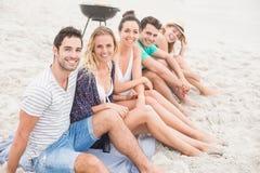 Groupe d'amis s'asseyant côte à côte sur la plage Photos libres de droits