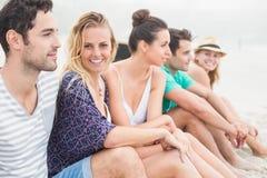 Groupe d'amis s'asseyant côte à côte sur la plage Photos stock