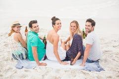 Groupe d'amis s'asseyant côte à côte sur la plage avec des bouteilles à bière Photographie stock libre de droits